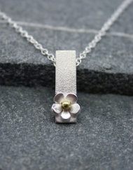 silver daisy drop necklace with a brass centre
