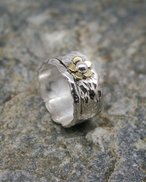 wide silver ring with brass flower and silver detail