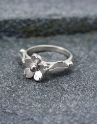 Silver daisy ring with leaf shoulders